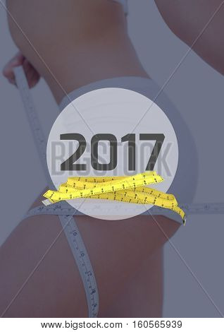 Mid section of woman measuring her thigh against 2017