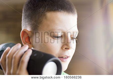 Young Boy Listening Music On Wireless Speaker