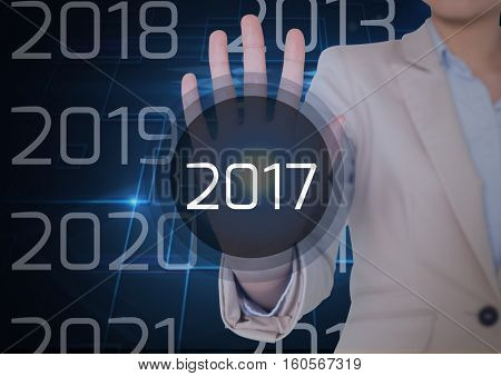 Mid section of business woman in digitally generated background touching 2017 new year message