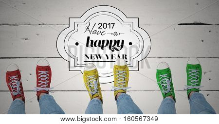 2017 new year wishes with teenagers wearing colourful sneakers on wooden background