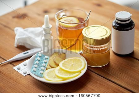 healthcare, traditional medicine and flu concept - drugs, thermometer, honey and cup of tea on wooden table