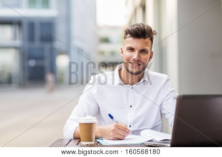 business, education, technology and people concept - young man with laptop computer, documents and coffee cup at city street cafe