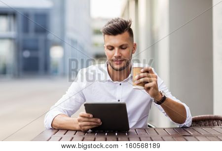business, technology and people concept - young man with tablet pc computer and coffee cup at city street cafe