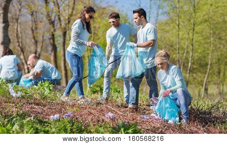 volunteering, charity, cleaning, people and ecology concept - group of happy volunteers with garbage bags cleaning area in park