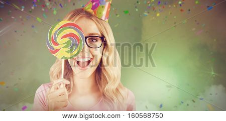 Portrait of a hipster hiding herself behind a lollipop against smoke at illuminated disco