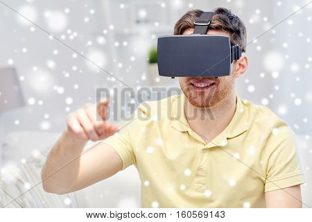 technology, augmented reality, winter, christmas and people concept - happy young man with virtual headset or 3d glasses playing video game over snow