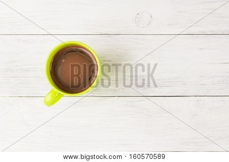 Green Cup Of Coffee Stands On A Wooden White Table