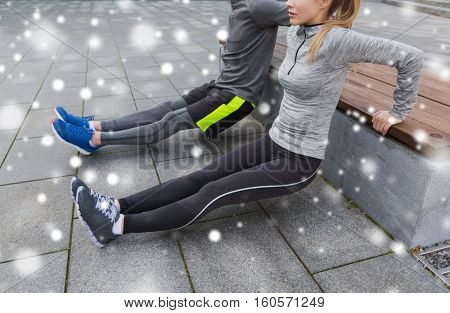 fitness, sport, exercising, training and people concept - couple of sportsmen doing triceps dip exercise on city street bench over snow