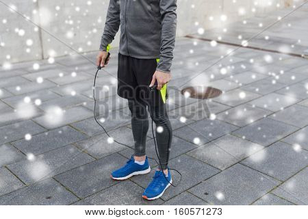 fitness, sport, people and healthy lifestyle concept - close up of man exercising with jump-rope over snow