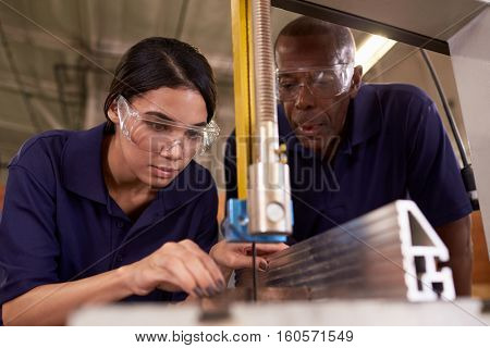 Carpenter Training Female Apprentice To Use Mechanized Saw