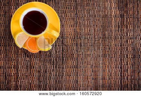 yellow coffee Cup on a bamboo napkin