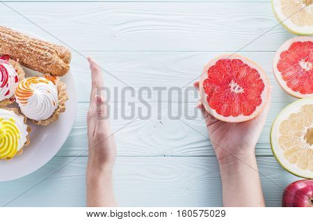 Hands of a young woman holding a grapefruit. Woman making a choice between sweets and fruits made a choice in favor of fruits and holding half a grapefruit. Unhealthy vs healthy food top view.