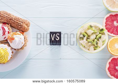 Choosing between Fruits and Sweets. Healthy versus unhealthy food. Weight Loss. Unhealthy tempting cakes and healthy fruit salad and fruits.