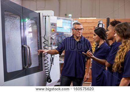 Engineer Training Apprentices On CNC Machine