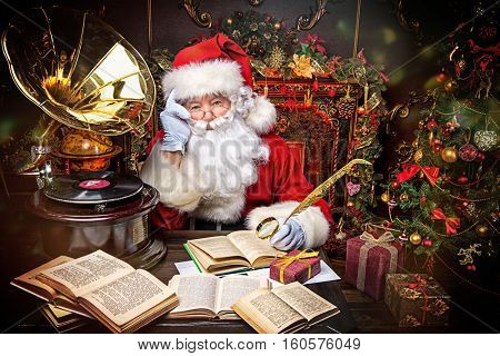 Good old Santa Claus reading a book and listening to old gramophone at home. Christmas songs. Christmas concept.