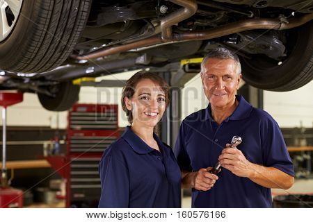 Male And Female Mechanics Working Underneath Car Together
