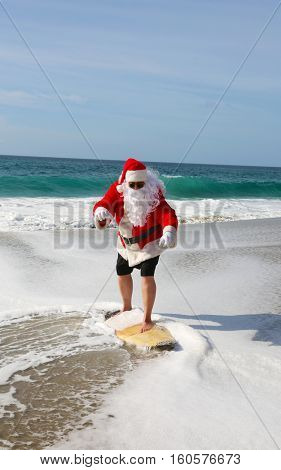 Christmas Surfing Santa Claus on the beach and in the ocean. Santa loves to surf the waves and hang 10.