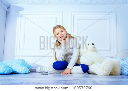 Happy 7 year old girl wearing knitted clothes sitting on a floor with her teddy bear and smart phone. Children's fashion.