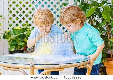 Two happy toddler kid boys making experiment with colorful soap bubbles and water, outdoors. Funny children, siblings, having fun with playing on warm day. Creative leisure for kids.