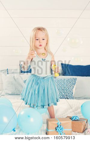 Cute Child Blowing Bubbles. Little Girl at Home. Children's Holiday