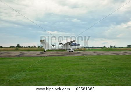 Kiev Region Ukraine - July 19 2014: Light private twin-engine plane is taking off from the runway with stormy sky on sunset on the background. Blurry background due to panning while shooting at long exposure