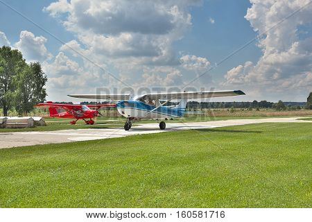Kiev Region Ukraine - July 20 2014: Light private planes on the airfield on a sunny day performing leisure flights. Cessna 150 two-seat general aviation plane on the front