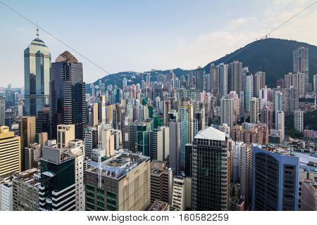 Residential buildings and modern office buildings near green mountain in Hong Kong, China, view from China Merchants Tower