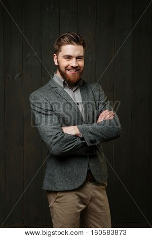 Portrait of a smiling young man in casual suit standing with arms folded isolated on the black wooden background