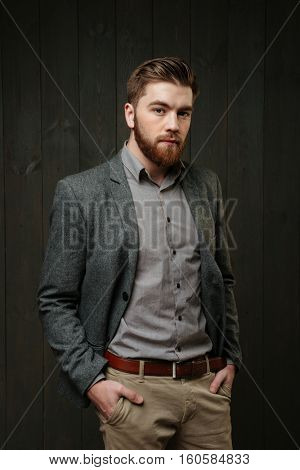 Portrait of a handsome bearded man in casual suit standing holding arms in pockets isolated on the black wooden background