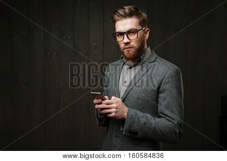 Portrait of a serious smart man in casual suit and eyeglasses holding mobile phone and looking at camera isolated on the black wooden background