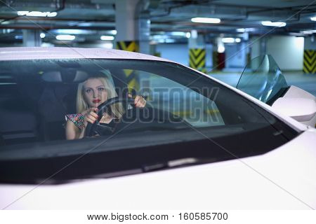 Pretty blonde woman with red lips sits in modern white car in parking