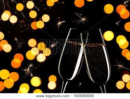 .   Celebration on New Year's Eve.  Close up of two glasses of Champagne clinking together.