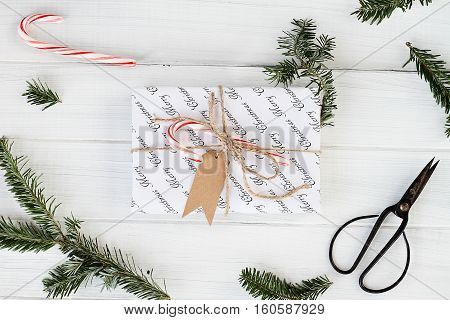 Beautiful Christmas gift with blank tag. Decorated naturally with candy canes pine tree twigs and twine over a white background with candy canes. Image shot from above.