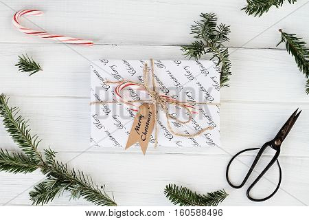 Beautiful gift with Merry Christmas tag. Decorated naturally with candy canes pine tree twigs and twine over a white background with candy canes. Image shot from above.