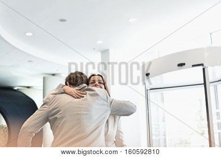 Business people embracing at brightly lit convention center