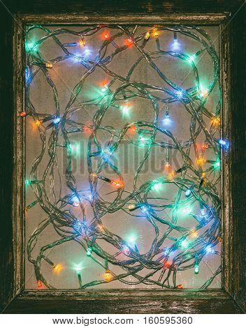 Colored lights festive Christmas garland in an old wooden frame. The concept of a New year tinted photo