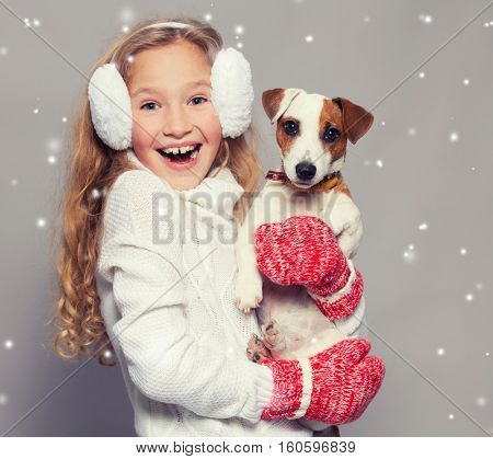 Girl with dog in winter clothes. Happy child. Studio shot
