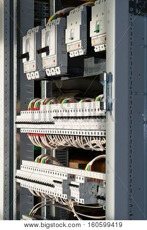 Connecting cables with cable lugs to circuit breakers in the electrical control panel on the artboard. Alignment of the components to ensure safety and reliability.