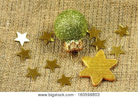 Christmas green bauble and gold stars on flax texture