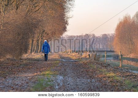 Woman with blue jacket and woolen cap walking on path in rural landscape.