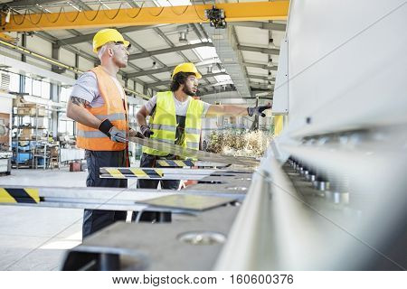 Male manual workers manufacturing sheet metal at industry