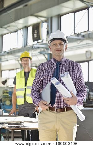 Portrait of confident male architect holding blueprints and laptop with worker in background at industry