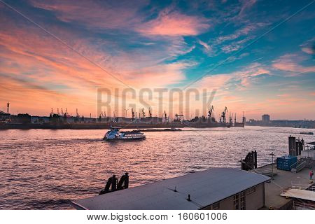 Hamburg, Germany - November 01, 2015: A lonely sightseeing ship passes along the silhouette of the famous docks of the harbor of Hamburg during a scenic sundown.