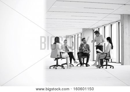 Mature businessman discussing with team sitting on chair in new office