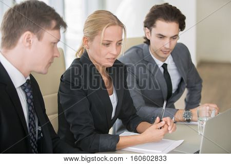 Group of three business partners discussing new project at meeting in office room, using laptop. Middle aged businesswoman explaining ideas, looking presentation on screen. Business success concept