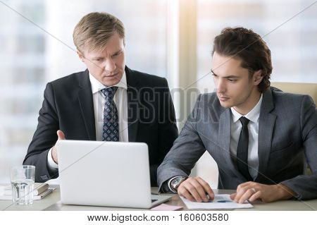 Group of two business partners discussing new project at meeting in office room, using laptop. Middle aged businessman asking his young colleague to explain presentation idea. Business success concept