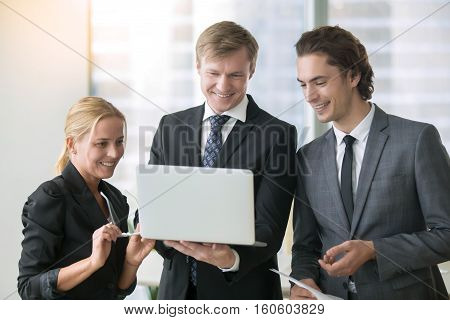 Group of three businesspeople discussing new project at meeting in office room, using laptop. Middle aged businessman leader showing work results to his team using laptop. Business success concept