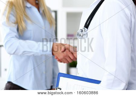 Female medicine doctor shake hand as hello with businesswoman in office closeup. Welcoming friend introduction or thanks gesture. Tests advertisement concept. Therapeutist ready to examine patient