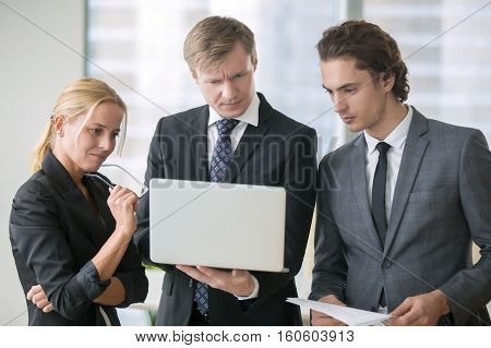 Group of three business partners discussing new project at meeting in office room, using laptop. Middle aged businessman focused on browsing presentation on laptop screen. Business vision concept