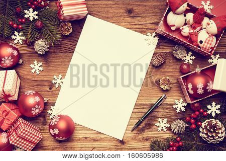 Letter to Santa Claus with Santa hat and red pencil on wooden background